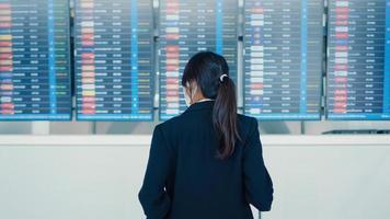chica de negocios asiática usa mascarilla con soporte de maleta frente a tablero mira la información que comprueba su vuelo en el aeropuerto internacional. pandemia de covid viajero de negocios, concepto de viajes de negocios. foto