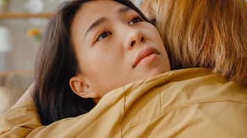 Sad young asian woman hug cuddle embracing with best friend in living room at home support each other with hard time with feel sick and bad, Relationship support concept. photo