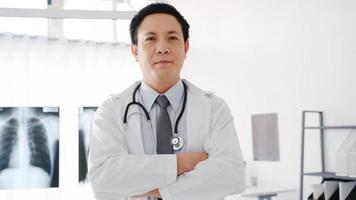 Joven médico de Asia en uniforme médico blanco con estetoscopio mirando a cámara, sonrisa y brazos cruzados durante la llamada de videoconferencia con el paciente en el hospital de salud. concepto de consulta y terapia. foto