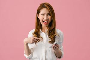 Sorprendió a la joven asiática que usa el teléfono móvil con expresión positiva, sonríe ampliamente, vestida con ropa casual y mirando a la cámara sobre fondo rosa. feliz adorable mujer alegre se regocija con el éxito. foto