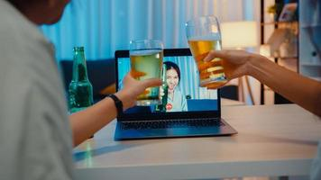 Young Asia female drinking beer having fun happy moment night party event online celebration via video call in living room at house at night. Social distancing, quarantine for coronavirus prevention. photo