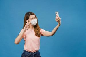 Smiling adorable Asian female wearing medical face mask making selfie photo on smart phone with positive expression in casual clothing and stand isolated on blue background.