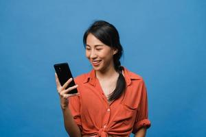 Jovencita asiática que usa el teléfono con expresión positiva, sonríe ampliamente, vestida con ropa informal sintiendo felicidad y parada aislada sobre fondo azul. feliz adorable mujer alegre se regocija con el éxito. foto