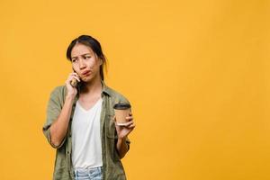 Jovencita asiática habla por teléfono y sostiene la taza de café con expresión negativa, gritos emocionados, llora enojado emocionalmente en ropa casual y se para aislado sobre fondo amarillo. concepto de expresión facial. foto