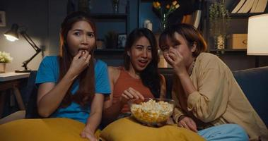 Group of attractive Asia lady girl freaking out fear and terrified moment eat popcorn watch horror online movie on couch in living room at home in night. Weekend lifestyle activity quarantine concept. photo