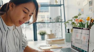 primer plano joven mujer de asia freelance focus teléfono móvil charla con colegas trabajo finanzas gráfico gráfico de cuenta plan de mercado en portátil en casa. alumna aprende en línea en casa, trabaja desde el concepto de hogar. foto