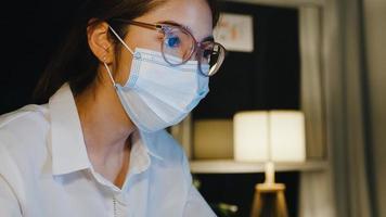 freelance asia lady use mascarilla médica use laptop trabajo duro en la sala de estar en casa. trabajo desde casa sobrecarga nocturna, trabajo a distancia, distanciamiento social, cuarentena para la prevención del coronavirus. foto