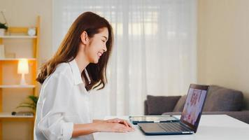 Young Asian business female using laptop video call talking with family dad and mom while working from home at living room. Self-isolation, social distancing, quarantine for coronavirus prevention. photo