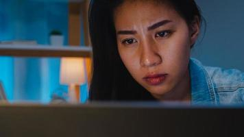 Joven empresaria china milenaria trabajando hasta altas horas de la noche con estrés con un problema de investigación del proyecto en la computadora portátil en la sala de estar de una casa moderna. concepto de síndrome de agotamiento ocupacional de personas de Asia. foto