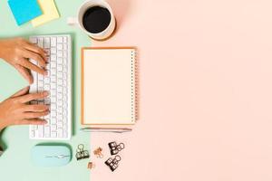 Foto creativa plana del escritorio del espacio de trabajo. escritorio de oficina de vista superior con teclado, mouse y cuaderno negro de maqueta abierta sobre fondo de color rosa verde pastel. vista superior maqueta con fotografía de espacio de copia.