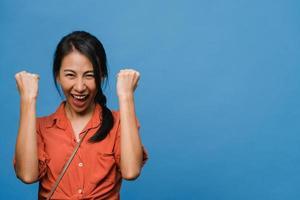 Jovencita asiática con expresión positiva, alegre y emocionante, vestida con ropa informal y mira a cámara sobre fondo azul. feliz adorable mujer alegre se regocija con el éxito. concepto de expresión facial. foto