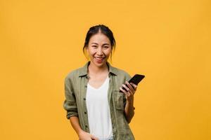 Sorprendió a la joven asiática que usa el teléfono móvil con expresión positiva, sonríe ampliamente, vestida con ropa casual y mirando a la cámara sobre fondo amarillo. feliz adorable mujer alegre se regocija con el éxito. foto