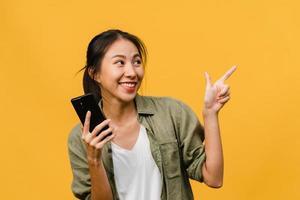 Retrato de una joven asiática que usa un teléfono móvil con una expresión alegre, muestra algo sorprendente en el espacio en blanco en ropa casual y se para aislado sobre fondo amarillo. concepto de expresión facial. foto