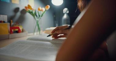 joven estudiante de asia adolescente lección de aprendizaje a distancia y hacer los deberes sentado en el escritorio en la sala de estar en la noche de la casa. trabajo desde casa, distanciamiento social, cuarentena para la prevención del coronavirus. foto