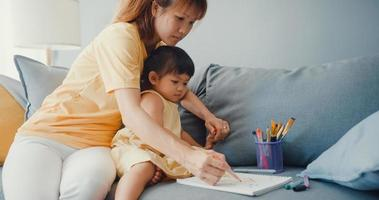 Happy cheerful Asia family mom teach girl paint use album and colourful pencils having fun relax on couch in living room at house. Spending time together, Social distance, Quarantine for coronavirus. photo