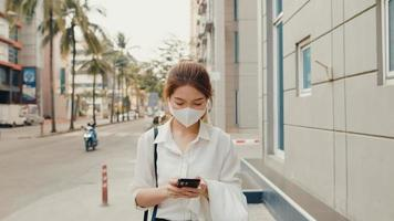 Successful young Asia businesswoman in fashion office clothes wearing medical face mask using smart phone while walking alone outdoors in urban modern city in the morning. Business on the go concept. photo