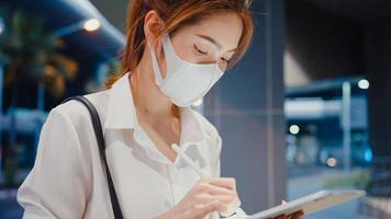 Young Asia businesswoman in fashion office clothes wear medical face mask using smart pen for write on digital tablet while sit alone outdoor in urban modern city at night. Business on the go concept. photo