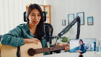 Influencer adolescente de asia tocar música de guitarra usar grabación de micrófono con teléfono inteligente para audiencia en línea escuchar en casa. Podcaster femenina hace podcast de audio desde su estudio en casa, concepto de estancia en casa. foto