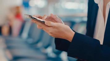 Close-up asiática mujer de negocios traje de desgaste del viajero sentado en el banco uso de reserva de teléfono inteligente billete de espera para el vuelo en el aeropuerto. viajero de viajes de negocios en la pandemia de covid, concepto de viajes de negocios. foto