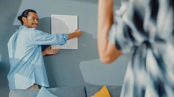 Feliz pareja joven y atractiva asiática hombre y mujer se ayudan mutuamente a colgar el marco de la imagen en la pared para decorar la casa y el paquete de caja de cartón en la sala de estar. concepto de hogar de decoración asiática joven casada. foto