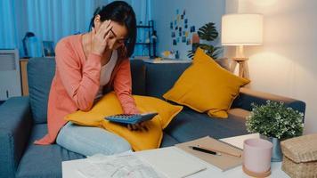 Señora asiática se siente estresada y preocupada con la factura y la factura de la tarjeta de crédito calculando el préstamo en el sofá de casa. estrés del préstamo hipotecario, obtener un préstamo sin trabajo, préstamos por dificultades relacionadas con el coronavirus, no se puede hacer el concepto de pago del préstamo. foto