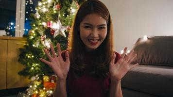 joven mujer asiática vlogger mira a cámara videollamada hablar con pareja, árbol de Navidad decorado con adornos en la sala de estar en casa. distanciamiento social, noche de navidad y fiesta de fin de año. foto
