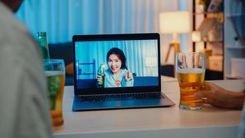 Joven mujer asiática bebiendo cerveza divirtiéndose feliz momento fiesta nocturna evento celebración en línea a través de videollamada en la sala de estar de la casa por la noche. distanciamiento social, cuarentena para la prevención del coronavirus. foto