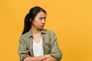 Retrato de joven asiática con expresión negativa, gritos emocionados, llorando emocionalmente enojado en ropa casual aislado sobre fondo amarillo con espacio de copia en blanco. concepto de expresión facial. foto