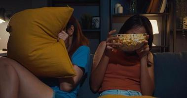 Attractive Asia couple ladies feel shock and fear moment eat popcorn watch horror online movie entertainment on sofa  in living room at home dark night. Weekend lifestyle activity quarantine concept. photo