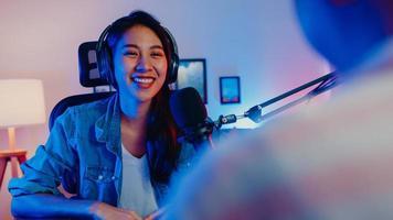 feliz asia girl host record podcast use micrófono use auriculares con laptop entrevista invitada conversación para contenido en su estudio en casa por la noche. concepto de equipo de sonido. concepto de creador de contenido. foto