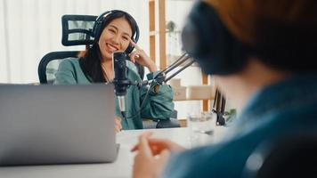 Asia girl radio host record podcast use microphone wear headphone interview celebrity guest content conversation talk and listen in her room. Audio podcast from home, Sound equipment concept. photo
