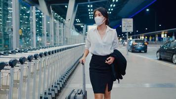 Chica de negocios asiática llega a destino, usa mascarilla con equipaje de arrastre, camina afuera, espera, terminal de autos en el aeropuerto nacional. pandemia de covid viajero de negocios, concepto de distanciamiento social de viajes de negocios. foto