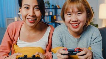 Lesbian LGBTQ women couple play video game at home. Young Asia lady using wireless controller having funny happy moment on sofa in living room at night. They have great and fun time celebrate holiday. photo