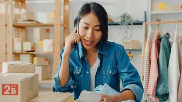 Young Asia businesswoman using smartphone call receiving purchase order and check product on stock work at home office. Small business owner, online market delivery, lifestyle freelance concept. photo