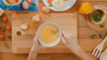 Hands of young Asian woman chef whisking egg into ceramic bowl cook omelette with vegetables on wooden board on kitchen table in house. Lifestyle healthy eat and traditional bakery. Top view shot. photo