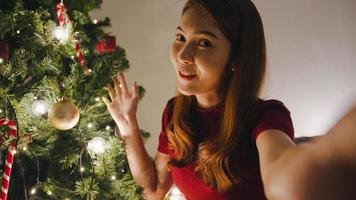 Young Asia female using smart phone video call talking with couple, Christmas tree decorated with ornament in living room at home. Social distancing, Christmas night and New Year holiday festival. photo