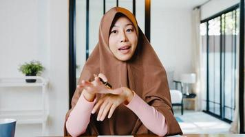 Asia muslim lady wear hijab using computer laptop talk to colleagues about plan in video call meeting while remotely work from home at living room. Social distancing, quarantine for corona virus. photo