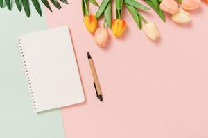 Creative flat lay of travel vacation spring or summer tropical fashion. Top view beach accessories open mockup black notebook for text on pastel background. Top view mock up copy space photography. photo