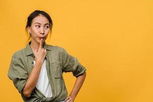 Retrato de joven asiática con expresión positiva, piensa en las próximas vacaciones, vestida con ropa casual sobre fondo amarillo con espacio de copia en blanco. feliz adorable mujer alegre se regocija con el éxito. foto