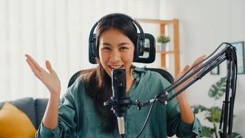 feliz niña asiática grabar un podcast con auriculares y micrófono, mirar a la cámara, hablar y descansar en su habitación. Podcaster femenina hace podcast de audio desde su estudio en casa, permanece en el concepto de casa. foto