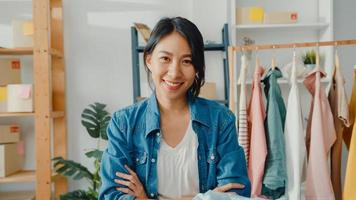Portrait of young Asia lady fashion designer feeling happy smile, arms crossed and looking to camera while working clothing store in home office. Small business owner, online market delivery concept. photo