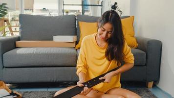 Feliz joven asiática desempacando la caja y leyendo las instrucciones para ensamblar muebles nuevos decorar la mesa de construcción de la casa con caja de cartón en la sala de estar de casa. foto