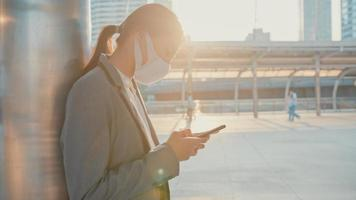 Young Asia businesswoman in fashion office clothes wear medical face mask using phone while walk alone outdoor in urban city. Business on go, Social distancing to prevent spread of COVID-19 concept. photo