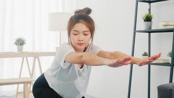 Young Korean lady in sportswear exercises doing working out and using laptop to watching yoga video tutorial at home. Distant training with personal trainer, social distance, online education concept. photo