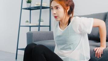 Young Korean lady in sportswear exercises doing working out doing tricep dips leaning on couch in living room at home. Social distance, Isolation during the virus. Exercises for the lower body. photo