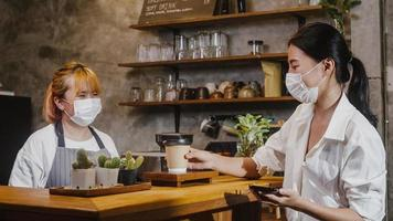 Young Asia female barista wear face mask serving take away hot coffee paper cup to consumer at cafe. Owner small business, lifestyle new normal after corona virus and social distancing concept. photo