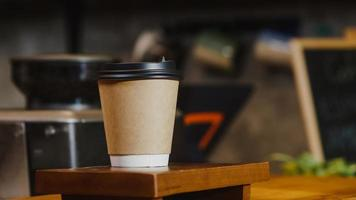Take away hot coffee paper cup to consumer standing behind bar counter at cafe restaurant. Owner small business, food and drink, service mind concept. photo
