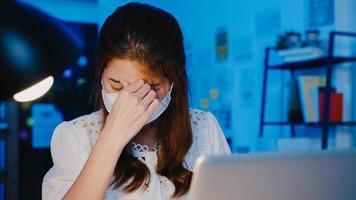 mujeres asiáticas independientes usan mascarilla usando una computadora portátil en el trabajo duro en la nueva oficina en casa normal. trabajando desde la sobrecarga de la casa por la noche, autoaislamiento, distanciamiento social, cuarentena para la prevención del virus corona. foto