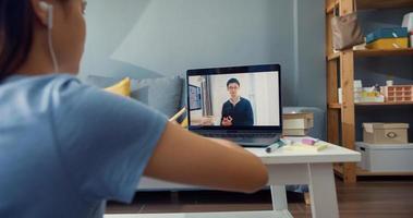 Close-up joven asiática con auriculares de uso casual usar videollamada de computadora portátil aprender en línea con un tutor en la sala de estar de la casa. Aislar el concepto de pandemia de coronavirus de educación en línea e-learning. foto