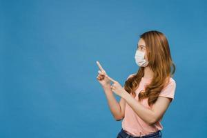 La joven muchacha asiática usa una mascarilla médica que muestra algo en el espacio en blanco vestida con ropa casual y mira a la cámara aislada sobre fondo azul. distanciamiento social, cuarentena por coronavirus. foto